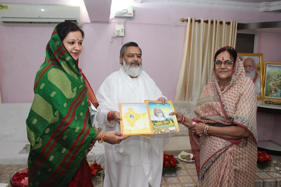 Brahmachari Girish Ji is presenting Maharishi Ji's books to Smt. Sushila Singh, Ex-Mayor of Jabalpur and her daughter-in-law.