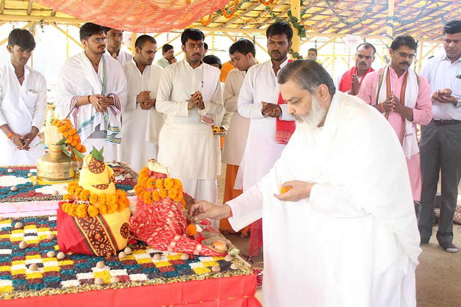Brahmachari Girish Ji is offering flowers and performing aarti at